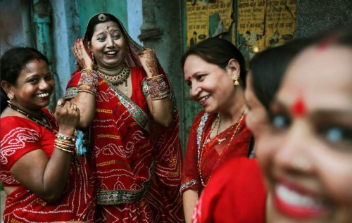 fotojournalismus:  Hindu women at a temple in New Delhi after participating in a procession that was part of Ganga Dussehra, a major Hindu festival, May 31, 2012. Hindus celebrate Ganga Dussehra by worshiping the River Ganges, consider the holiest river.   [Credit : Kevin Frayer/AP]