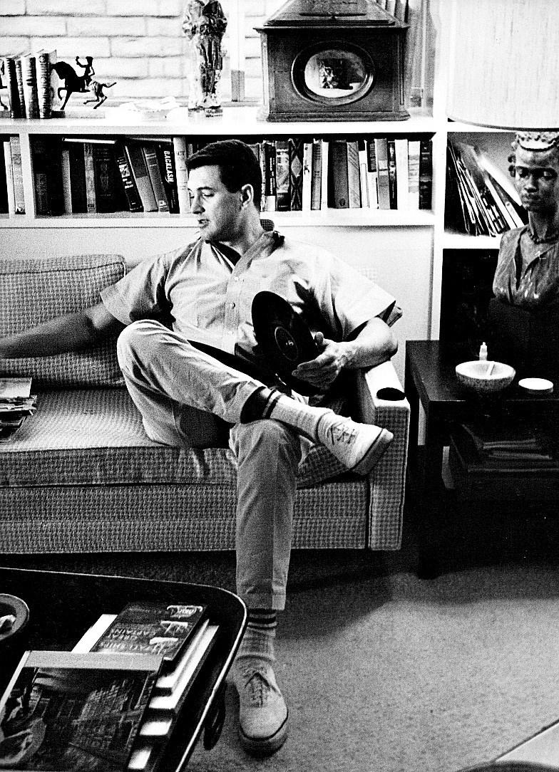 Rock Hudson at home with his record collection, 1950s.