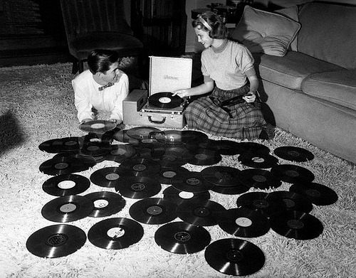 cuntbarf:  Young couple playing records spread out on living room floor. Ohio, 1955.