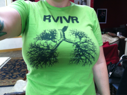 Day 126: RVIVR. I got this shirt at Awesome Fest 4 in San Diego, CA in September of 2010! It was I think my first time seeing RVIVR and I was really impressed. I had listened to them before but seeing them live was really intense and everyone had so much fun, so I needed a shirt and an LP. They played at that bar with the comfy red booths, I can't remember what it's called right now because I'm on the bus. Oh I remembered it's called the office! I wore this shirt on the way home from San Diego, I was driving Avi's moms minivan and wearing some lime green framed glasses too, and Matt kept freaking out about how the light reflecting off the shirt was making my skin look green and he took probably 20 pictures of me trying to capture exactly how green I was.