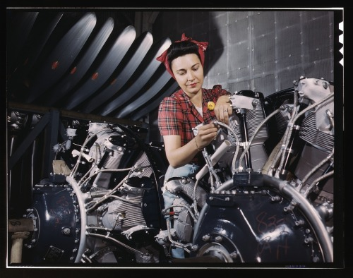 Woman working on an airplane motor at North American Aviation plant in California.   June 1942