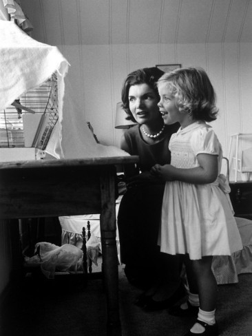 Jackie and her daughter Caroline watching a bird in a cage at home. Photographed by Alfred Eisenstaedt.