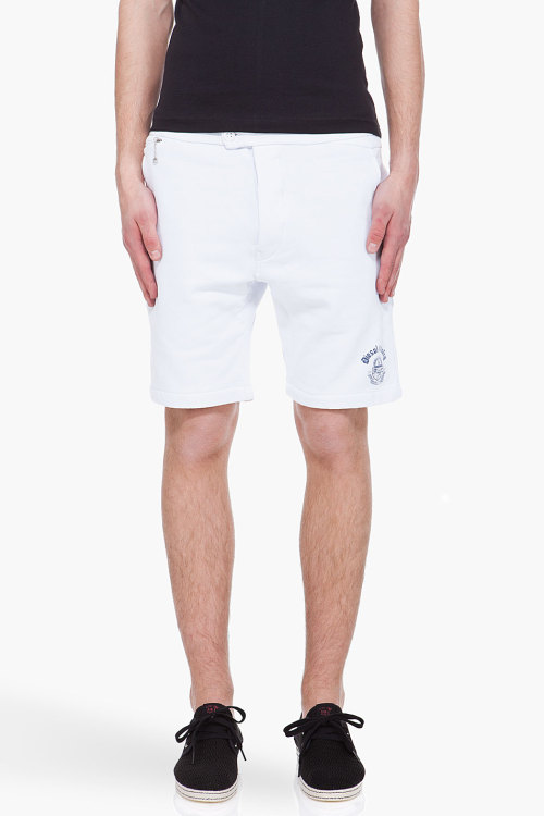 White Chi Blado Sweat Shorts by DieselSlim fit shorts in white. Adjustable button tab at waist. Five pocket styling. Silver tone zip and chain detail at coin pocket. Vertical darts at rear. Tone on tone stitching. Button fly. 100% cotton. Machine wash cold.