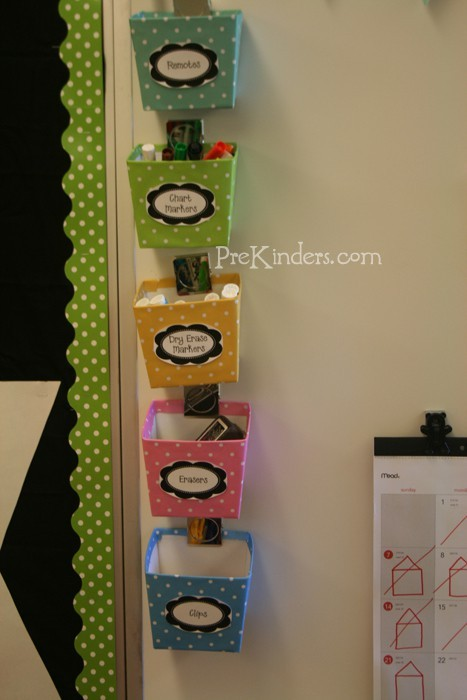 boxes from the Target Dollar Spot, covered them polka dot scrapbook paper, and attached them to white board with magnetic clips. They hold my remotes, chart markers, dry erase markers, erasers, and board clips.