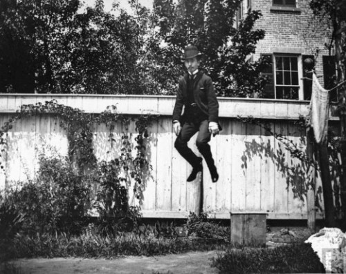 A man in a suit and bowler hat jumping in the air in a backyard in Brooklyn, New York, 1890.