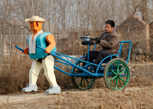 reblololo:  Farmer Wu Yulu drives his rickshaw pulled by a his self-made walking robot near his home in a village at the outskirts of Beijing, on January 8, 2009. This robot is the latest and largest development of hobby inventor Wu, who started to build robots in 1986, made of wire, metal, screws and nails found in rubbish sites. (Reuters/Reinhard Krause)