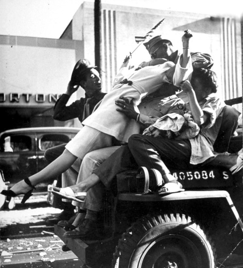"Title: ""Jubilant soldier kissing flag-waving woman as they ride on hood of a military jeep during impromptu celebration of the end of WWII following the surrender of Japan."" Date: August 14, 1945 Location: Hollywood, CA Photographer: Walter Sanders"
