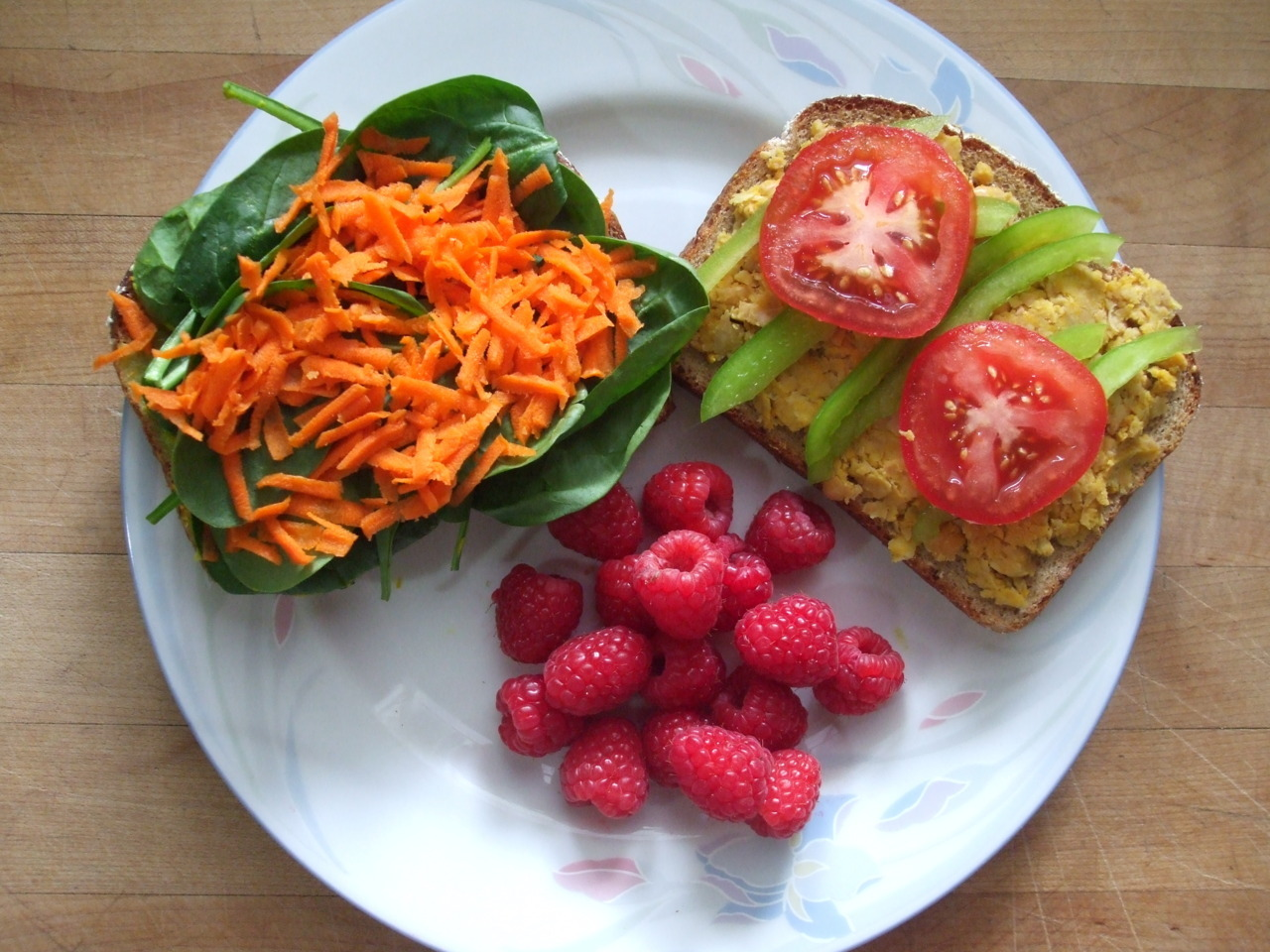 whole grain sandwich with guacamole, mustard, spinach, carrot, green pepper, tomato, sliced tofurky kielbasa, chickpeas mashed with soy sauce, and raspberries.