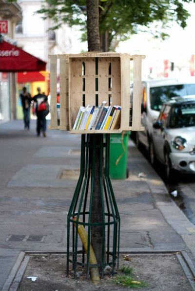 "unconsumption:  We're fans of free book exchanges, like the Little Free Libraries; the now-defunct-phone-booths-turned-mini-libraries (here, here, here, here, and here); shelves in London Tube and train stations and in airports that enable travelers to swap books; former newspaper racks; and a 1979 Ford transformed into a bookmobile from which free books are distributed in Buenos Aires, among others, that spring up in public spaces.  (We're also fond of more traditional libraries that are housed in non-traditional settings like repurposed old buses and historic barns and churches.) And now in Paris, there's this communal book exchange sitting atop a tree cage:   Strasbourg-based street artist Florian Rivière is back with a new, neat urban intervention! Last weekend, Rivière installed a little library on a sidewalk near Gare du Nord … .  I don't know if that's a pallet or a crate (or both), but I like it! See a couple of Riviere's other urban interventions, a.k.a., ""hacktions,"" here. (via Urban Hacktivist Launches Street Library — The Pop-Up City)"