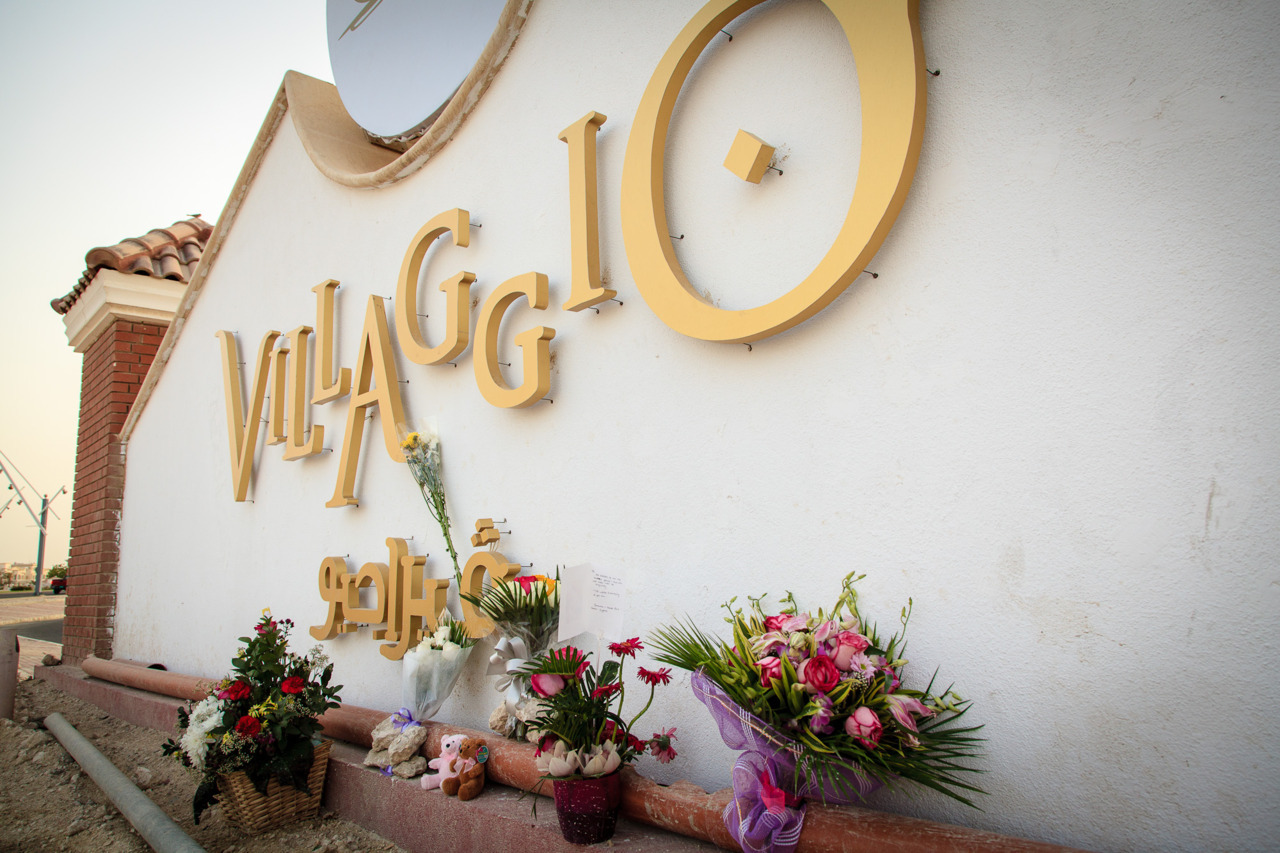Remembering the fire,  by Omar Chatriwala. Flowers are left at the Villaggio Mall sign to remember the victims of Monday's fire that left 19 people dead, including 13 children.