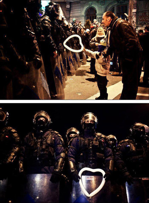 Romanian child hands a heart-shaped balloon to riot police during protests against austerity measures in Bucharest.