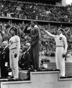 The 1936 Berlin Olympic Games were marked by Hitler's desire to showcase Aryan supremacy and American Jesse Owens' refusal to play along. Owens won four gold medals at the games including the long jump. This photo from the medal stand of that event is one of the most powerful images in Olympic history.