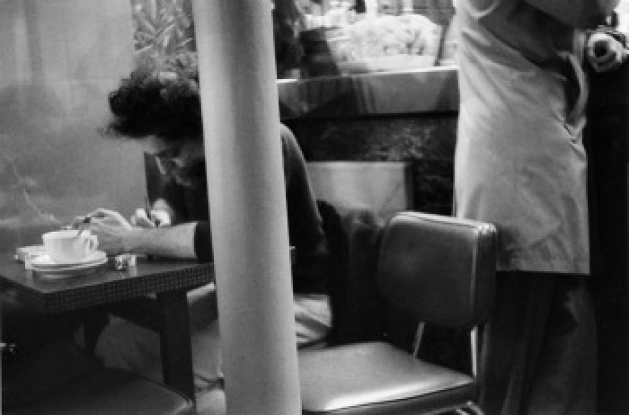 Georges Perec at Place Saint-Sulpice cafè, photo by Pierre Getzler  October 1974, Saint-Sulpice Square in Paris. A man is sitting on a terrace. On his table there's a notebook, which he is conscientiously filling in with everything happening in front of him: letters, like K, L, M, or P (for parking). Symbols, and numbers: 86 for the bus, a 6 that indicates that we are in the 6th district in Paris; fugitive slogans from advertising; a stone for the fountain; the church, buildings; trees; a piece of sky; pigeons; vehicles; human beings; dogs; bread (Baguette), a salad. Colors: red for cars, blue for bags, green for shoes, blue for taxis.   Simultaneousness of actions or micro events: postures, gestures, discussions with two, three, sometimes more people; a man with a briefcase, two men smoking pipes, a woman with a coat, people that are gathering in front of the church, a man with a bow tie, three children coming from school, a priest, a man stopping to stroke a dog, a woman waiting for a taxi, two beaming Japanese tourists, a couple, a man with tics, a policeman with a bike. Every kind of activity: to wait, to stroll, to wander, to walk, to run, to go, to look for something, to hesitate, to stay, to wait for the bus, to stand, to get up.   Elements like a fountain, a kiosk, and a group of trees are all standing at a center. The surroundings are historical buildings, with a church on one side. There is a possibility to make a plan, to make an order, a framework with elements fixed in space, grounded in space, lifeless: Saint Sulpice Square is organized as a cube.