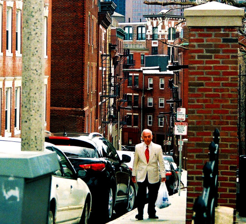Old Man walking up big hill. Boston MA.