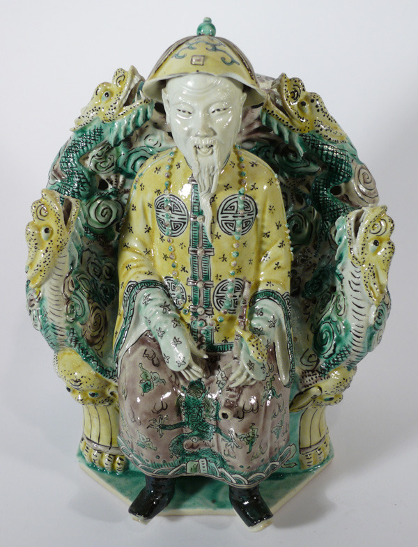 A BISCUIT FAMILLE VERTE FIGURE OF THE KANGXI EMPEROR, SEATED ON A THRONE AND PAINTED IN THE THREE SANCAI COLOURS (SMALL DENTS ON THE HAT), CHINA, QING DYNASTY, KANGXI PERIOD (1662-1722) via