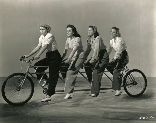 Cecilia Parker, Peggy Moran, Frances Rafferty and Frances Raeburn ride a bike.