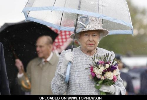 theumbrellacollection:  Queen Elizabeth II shelters under an umbrella during a hailstorm as she visits the 'Wild London' exhibition with Prince Philip, Duke of Edinburgh on May 15, 2012 in Richmond, England. (Photo by Suzanne Plunkett - WPA Pool/Getty Images)