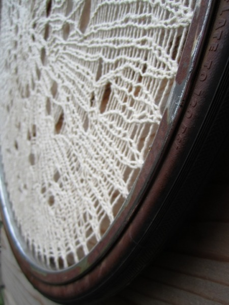 a bicycle wheel with the spokes removed as the frame for hand knit lace in cotton yarn.