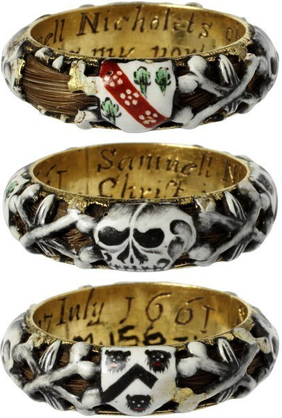 amy-addams: This enamelled gold mourning ring commemorates the death of Samuel Nicholets of Hertfordshire who died on 7th July 1661, as is recorded in the inscription inside the ring. The ring is hollow, and a lock of hair curls around within it, visible through the openwork of the enamelled decoration of skulls and coats of arms