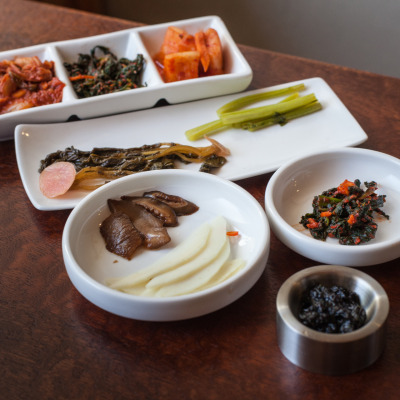 Assorted pickled vegetables from FuseBox, including Kimchee (Napa Cabbage, Radish Greens and Daikon), Radish Crowns and Tokio Turnip Stems, Shitake Mushrooms and Green Mango, and Pickled Nori.