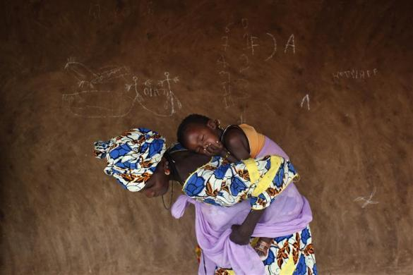 lifeisliterallylimited:  A woman wraps her sleeping baby on her back after a talk with members of the Spanish Non-Governmental Organization Accion contra el Hambre (Action against hunger) about good sanitation and hygiene practices in Niomel, in the Guidimakha region, Mauritania June 3, 2012. REUTERS/Susana Vera