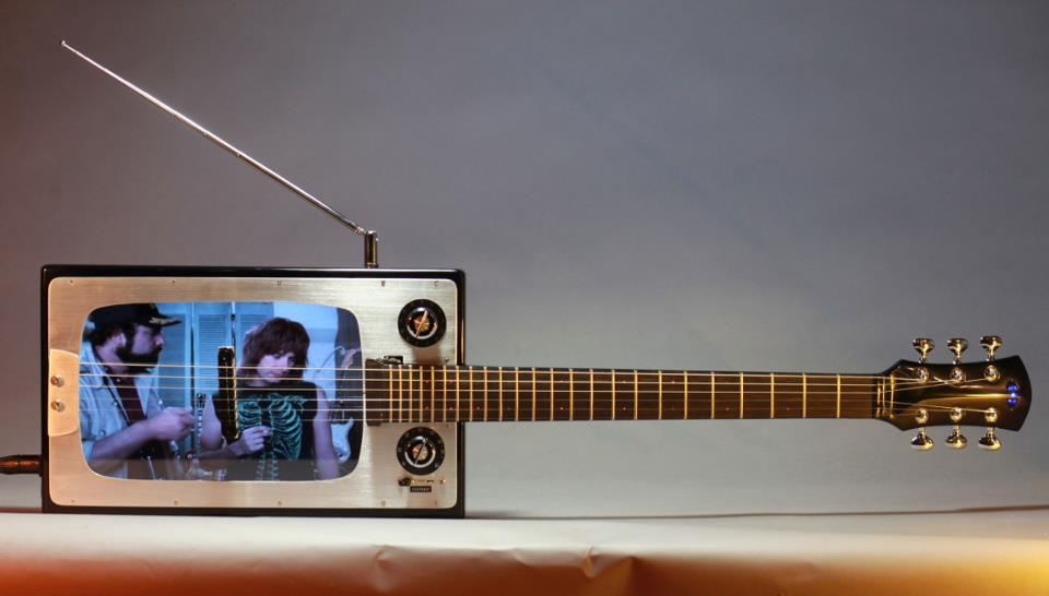 ": Visionary Instruments- ""Retro TV Guitar"". . Visionary Instruments luthier Ben Lewry crafts high-end guitars that incorporate video displays into their bodies. His latest creation, the Retro TV guitar, uses actual parts from a vintage television set and incorporates them into a solid body instrument. The guitar uses piezo pickups fixed atop the screen, and actual TV knobs are used for tone and volume- as well as for changing the channels and the actual video footage displayed on the guitar. . The body takes its inspiration from Bo Diddley's famed rectangular guitar, while the fretboard features fiber optic markers, and the headstock has Gotoh tuners and an illuminated logo. For more on the Retro TV guitar (including ordering information) and other Visionary Instruments guitars, click here!"