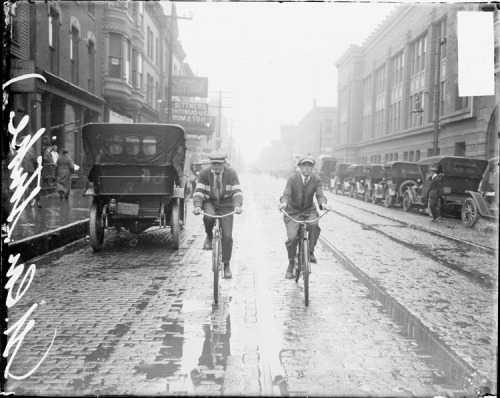 Two boys ride bikes along a street in the rain during a street car strike in Chicago, c. June 1915. Photograph from the Chicago Daily News.  Want a copy of this photo?  > Visit our Rights and Reproductions Department and give them this number: DN-0064589. Connect with the Museum