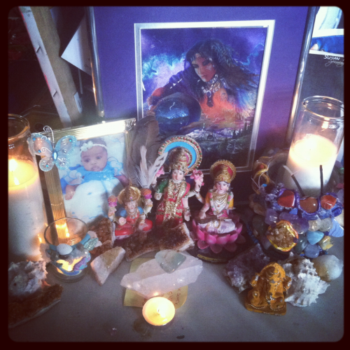 In honor of the divine light energies coming to earth . I set up this altar at my work desk to receive the energies from the divine mother.  Reprinted with permission of Red Wheel/Weiser.  When a woman creates an altar, she re-collects the scattered parts of herself, reconnects with her inner beauty, and reflects on the Essential Feminine within her psyche. Her altar represents her essential self and becomes a visual metaphor for her woman-spirit. A woman's altar is the bridge between her inner world and the world of form. It is where she is free to capture and display the shapes, the shades, and the substance of her invisible essence. Once she has created the altar, a woman depends on it to tell the story of her inner life. It is a place of her own where she can take time to make sense of the insane pace of her life, where she can find the space to simplify, where she can just sit and stare. The altar becomes a place where the woman can commune with both the personal and the cosmic aspects of herself, where she can both dance with the Divine and imbue every aspect of her personal life with sacredness, where she can both reclaim her power and revel in her innate beauty.  An altar can be used in many ways:   to say thank you to the powers that be to celebrate Mother Nature in all her guises to seek spiritual wisdom to honor the ancestors to offer up struggles to receive creative inspiration to dialogue with the deeper part of her being to honor her body  This is a partial list—the uses of the altar are limited only by a woman's imagination!