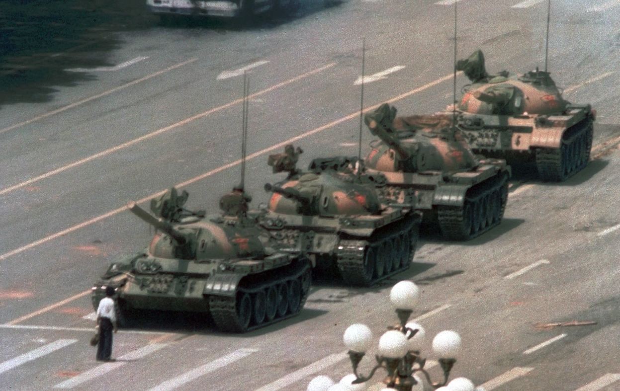 "atlanticinfocus:  From Tiananmen Square, Then and Now, one of 50 photos. Here, A Chinese man stands alone to block a line of tanks heading east on Beijing's Cangan Boulevard in Tiananmen Square, on on June 5, 1989. The man, calling for an end to violence and bloodshed against pro-democracy demonstrators, was pulled away by bystanders, and the tanks continued on their way. More on this iconic image and the still-anonymous ""tank man"" here. (AP Photo/Jeff Widener)   One of the best PBS Frontline's I've seen was the one on Tankman, exploring his possible identity, and the circumstances surrounding his legendary moment of protest.  It's still one of the most brass-ballsingly inspirational, purely heroic things I've ever seen, and the fact that his identity is still a mystery is remarkable. You can stream the episode in its entirety on the PBS site here."