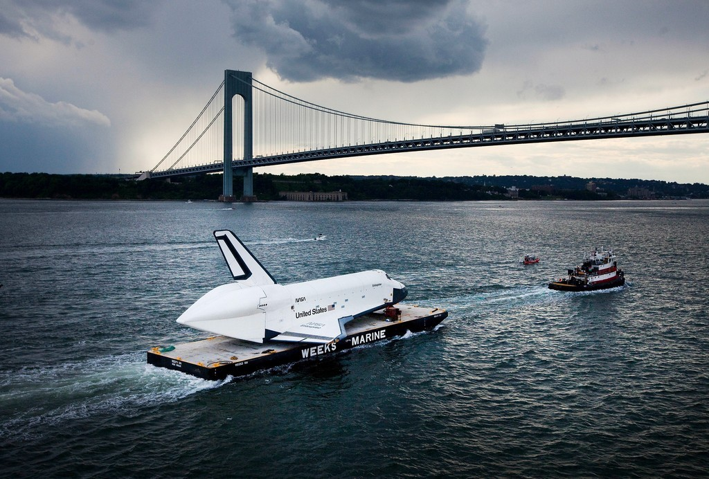 The Space Shuttle Enterprise is towed on a barge underneath the Verrazano-Narrows Bridge in New York City on its way to the Intrepid Sea, Air and Space Museum. The craft will dock at Port Elizabeth, New Jersey, on Sunday night before tomorrow's trip to the Manhattan's west side, and lifted onto its new home on the flight deck of the Intrepid.