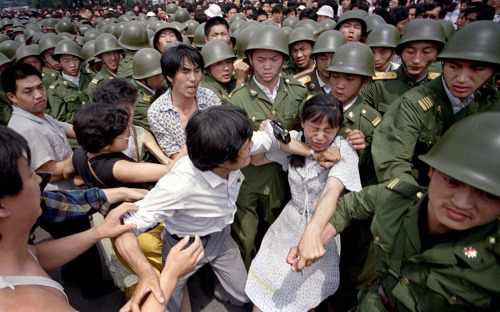A young woman is caught between civilians and Chinese soldiers, who were trying to remove her from an assembly near the Great Hall of the People in Beijing, on June 3, 1989. (AP Photo/Jeff Widener)