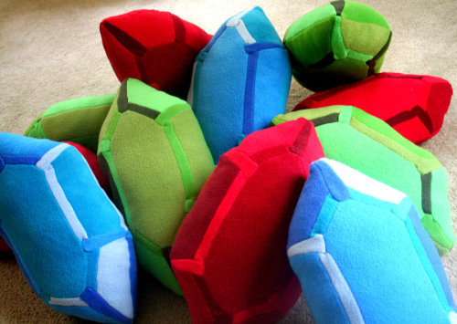 "dotcore:  Rupee Pillows.Available in green, blue and red, each rupee is made of 4 colors to emphasize a 3-dimensional quality. Made from fleece for superior snuggling comfort, each rupee measures roughly 20""x9""x5"". Available to purchase on Etsy."