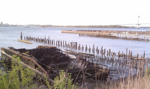 "A boat long decaying in College Point's northern shoreline with the Whitestone Bridge in the background.  The boat can be found as you walk along a public waterfront path of the Powell Cove Estates.  You can also see the remains of previous piers.  College Point was once home to numerous factories, allowing raw materials to come in and finished products to ship out with ease in the late 19c and early 20c.  The neighborhood was also a recreational getaway.  Ferries from Manhattan would shuttle people who would arrive to spend time in the numerous outdoor German beer gardens.  Unfortunately, none of those beer gardens exist today.  Even Mayor Fiorello LaGuardia spent the summer of 1937 in College Point, conducting the city's administrative business in a mansion by the water, eventually dubbed ""the Summer City Hall"". Powell Cove Boulevard, College Point"