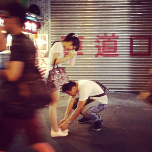"PHOTO OF THE WEEK : Taichung Moments  This photograph was taken at night on the streets of Taichung by Alamby of DigitlRev TV.  What we like about this photograph is that it's one of those ""magical moment"" street photos.  A boy bends down to tie his girlfriend's shoelace … the red Chinese characters on the shop's security grille, the neon lights, night shadows and the crowd walking by … a simple story told well. In Alamby's own words: ""This was a snapshot I took at Yizhong Night Market on the evening we arrived at Taichung. We just happened to walk past this lovely couple and the scene caught my eye. No technique or staging, it was just a simple click on my iPhone to capture a touching moment in a memorable city."" Want to know more and see the places visited by Alamby? Simply click here for details. Stay tuned for Friday's story and to learn more about Alamby's experiences in Taichung  **** Photo of The Week in July : ""Wandering Through Europe""Share your photos with Welcome Abroad and you could win a Cathay Pacific Holidays Cash Voucher!  Read the Rules of Submission then send your photograph to marketing@cxholidays.com *** If you are unsure about how to resize or optimize your photograph before submitting, please click here to read our simple FAQ."