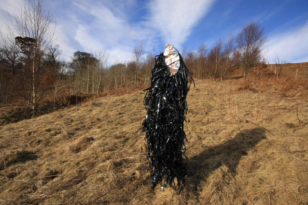Hoodoo, 2010 Performance at Campsie Glen, Scotland. Wearable sculpture of foil, neon stripe and video tape.