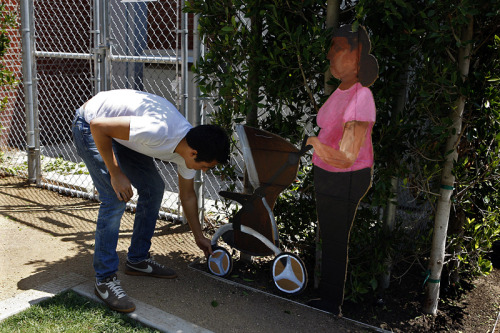 Artist pays homage to L.A.'s unseen workers: Ramiro Gomez's cardboard cutouts of nannies, gardeners, valets and housekeepers have appeared, in silent tribute, around the wealthy districts of the city.  Most pieces last a day or two if Gomez is lucky. Once, a valet parker he planted outside a lot near the Sunset Strip made it four days. Gomez writes his contact information on the back of each piece so people can tell him where the art ended up. So far, no one has reached out. At first it was tough to let go. He'd stand by for a while to see people's reactions, then take the cutout down and lug it back home. But then Gomez realized it was not his place to keep public art out of view. So he learned to walk away.  Photo: Ramiro Gomez attaches his painting of a nanny against a cyclone fence in West Hollywood Park. Credit: Genaro Molina / Los Angeles Times