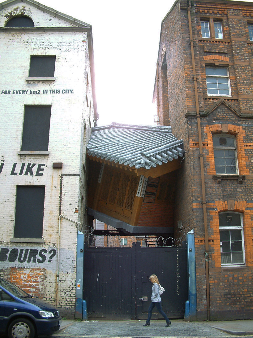 youmightfindyourself:  do ho suh's work 'bridging home' is an outdoor mixed-media installation built between two structures. the small house is built on an angle, seeming to hover several feet above the ground between two taller buildings. the perched piece has an unsettling affect, highlighting the tension existent between stranger-neighbors in larger cities, alluding to the dual sense of belonging and anonymity of an individual hailing from this place. 'bridging home' also explores the affect of living in an interconnected world upon the psychology of the individual and the community.
