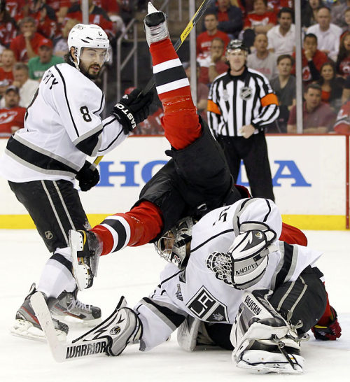 siphotos:  New Jersey's Patrik Elias face plants behind Kings goalie Jonathan Quick as Drew Doughty watches during Game 2 of the Stanley Cup Finals. The Kings won again on Monday to take a 3-0 series lead. Game 4 is Wednesday in Los Angeles. (Gary Hershorn/Reuters) FARBER: Kings pound Devils to close in on CupCAZENEUVE: Devils powerless against Kings