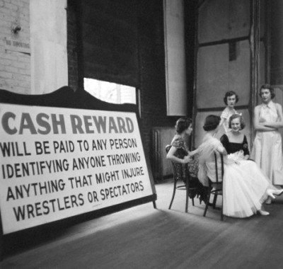 Women resting while paricipating in a fashion show at the Chicago Coliseum (which also hosted wrestling matches), 1954, Chicago.