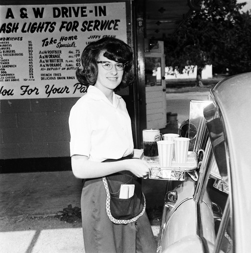 Teenage girl working as a car hop at an A&W Drive-in, 1964