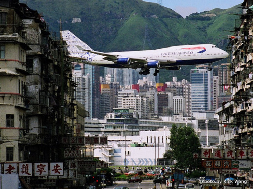 urbanterritory:  British Airways flight landing at Kai Tak Airport in the heart of Hong Kong.  Kai Tak was closed in July 1998 and replaced by Chep Lak Kok, 30 Km away, on Lantau Island. Clearance requirements for aircraft takeoffs and landings made it necessary to limit the height of buildings that could be built in Kowloon. Landings at Kai Tak must have been the most dramatic experience (if you had a window seat).  Awesome picture by Rick W on Flickr.