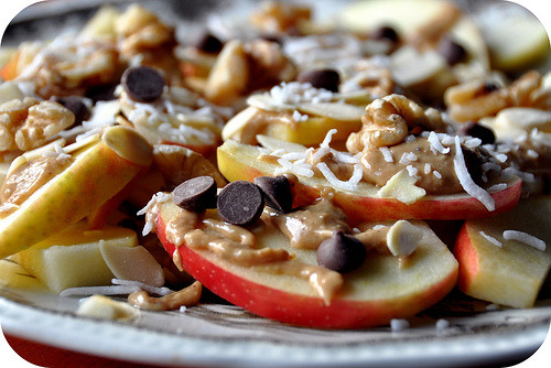 "nutritiongeek:  Apple Nachos | Manifestvegan  3 crispy and slightly tart apples 1 tsp lemon juice 3 tbsp creamy natural peanut butter 1/4 cup sliced almonds 1/4 cup pecans 1/4 cup flaked unsweetened coconut 1/4 cup vegan chocolate chips"" For these, I sliced up some apples thin enough so it would be easy to eat the slice in one or two bites. I also lightly spritzed the apples with lemon juice to keep them from browning too fast. Then I melted some peanut butter–until it was super runny–and drizzled it all over the apples. Next, I topped the apples and peanut butter with unsweetened flaked coconut, sliced almonds, a few pecans and, of course, chocolate chips. And finally, I drizzled a little more peanut butter onto the plate. Ya know, for good measure."""