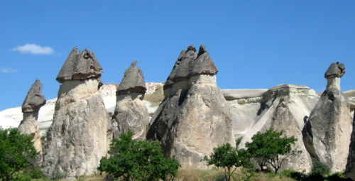"Fairy chimneys in Monks Valley. Monks Valley is located in Cappadocia, which is a touristic term for the central part of Turkey. Fairy chimneys have a thin layer of hard volcanic rock on top of a thicker layer of tuff, which is soft and easily eroded. The chimneys form when the softer rock is eroded away faster than the hard rock, until eventually the hard bit at the top of the ""chimney"" falls off."