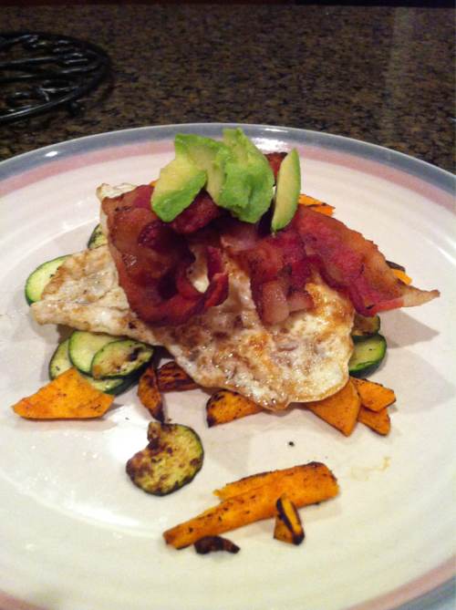 "Zucchini & Sweet Potato Stack topped with Dippin Eggs, Bacon, & Avocado   Why does egg yolk make everything so yummy?! Growing up my dad called over easy eggs ""dippin eggs"" because we would dip our sausage links or bacon in the yolks.   I made this delicious concoction for breakfast yesterday. It was super filling and tasted great. I'm a well done kinda girl so the charred, aka burned pieces, were part of my plan.   Yields 1 serving  2 slices nitrate free, sugar free bacon 2 cage free, organic eggs 1/2 cup sweet potato, thinly sliced 1/4 cup zucchini, thinly sliced 1/4 avocado, sliced Coconut Oil spray  1. In a large skillet, cook the bacon to desired crispiness. Set bacon aside on a paper towel to drain.   2. Drain the grease but leave about a teaspoon for cooking veggies. Combine sweet potatoes and zucchini in skillet. Cook over medium heat for 7-10 min until tender.   3. Arrange sweet potatoes and zuchini in a pile on a plate. Wipe skillet with a paper towel.   4. Spray light layer of coconut oil and fry eggs to desired taste. I prefer over medium.   5. Stack eggs on top of the sweet potatoes and zucchini. Top with bacon and avocado."