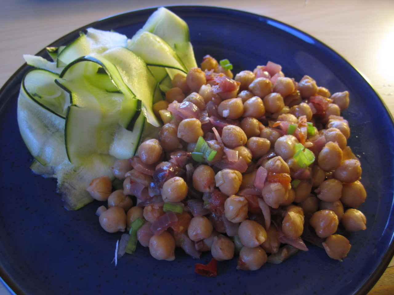 Summery chickpea stew with lemon courgette ribbons  The chickpea stew is a fun thing to be able to cook on the George! You start off by grilling a red onion, a few cloves of garlic, some chilli, 5 cherry tomatoes and a bit of vegetable oil for 10minutes. Then add a can of chickpeas and half a glass of rosé wine and cook for another 10minutes. It's best left for a while, resting on the turned-off grill and reheated 30minutes or so after, but you can eat it straight-away! Then add some spring onion at the end.   The courgette ribbons are done by using a vegetable peeler along the length of the courgette and then just dress with some fresh  lemon juice.   Grill love