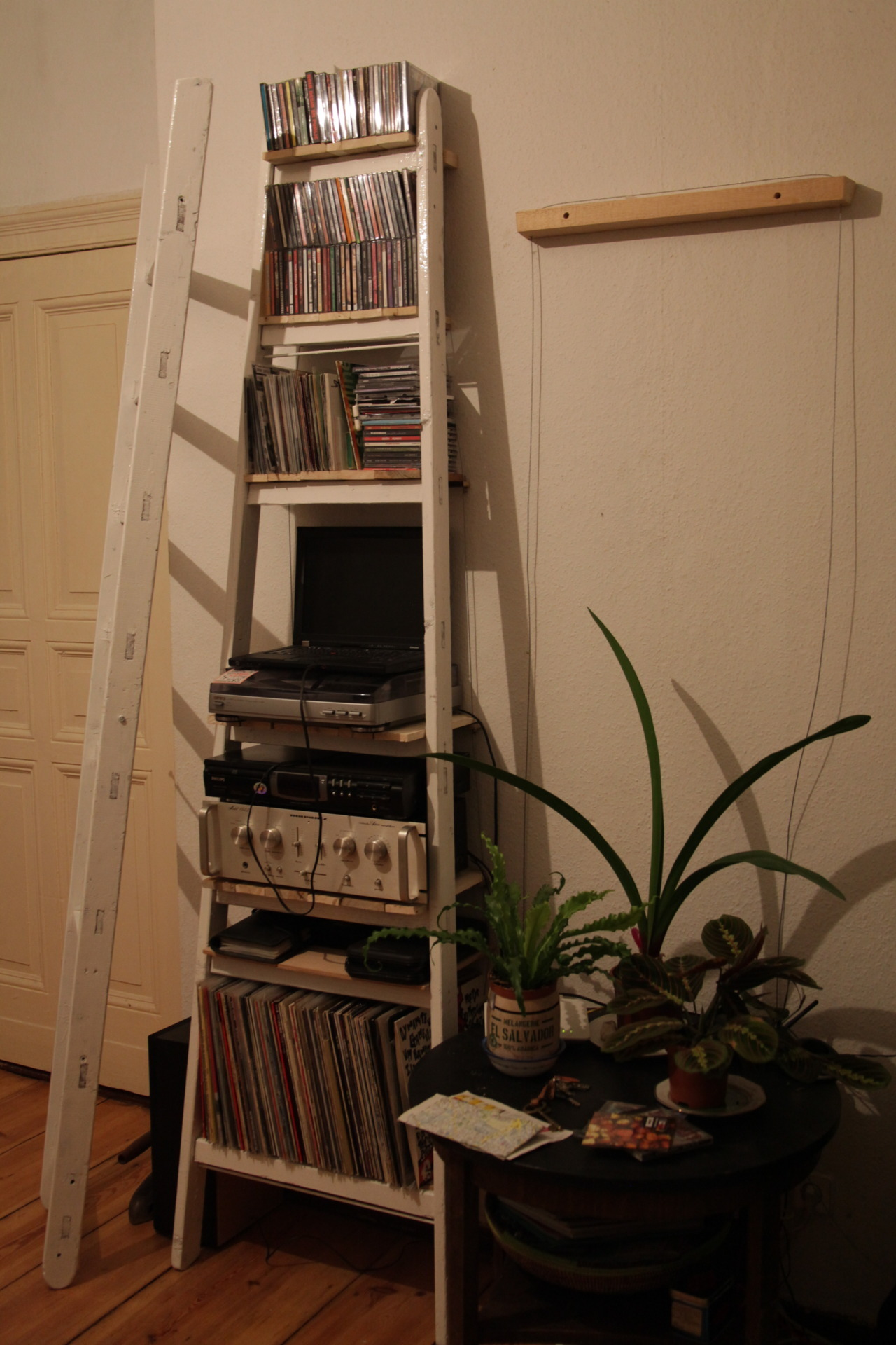 first side of our ladder shelf is up! made of an old ladder, found steel cable & shipping pallet wood