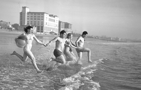 Four bathers running into the ocean at Santa Monica Beach, Calif., circa 1947.