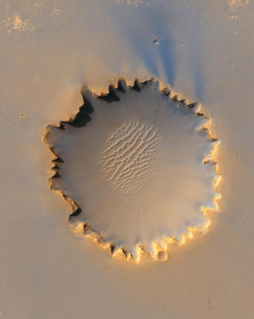 "Victoria Crater by HiRISE  This image from the High Resolution Imaging Science Experiment on NASA's Mars Reconnaissance Orbiter shows ""Victoria crater,"" an impact crater at Meridiani Planum, near the equator of Mars. The crater is approximately 800 meters (half a mile) in diameter. It has a distinctive scalloped shape to its rim, caused by erosion and downhill movement of crater wall material. Layered sedimentary rocks are exposed along the inner wall of the crater, and boulders that have fallen from the crater wall are visible on the crater floor. The floor of the crater is occupied by a striking field of sand dunes.  Lovely. Check out the high-res."
