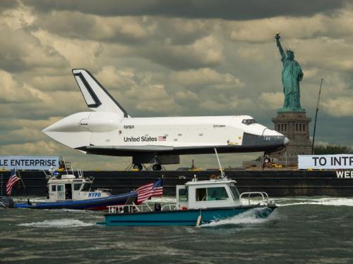 Atop a barge on Wednesday, June 6, 2012, the space shuttle Enterprise was towed on the Hudson River past the Statue of Liberty on its way to the Intrepid Sea, Air and Space Museum, where it will be permanently displayed. Image Credit: NASA/Bill Ingalls