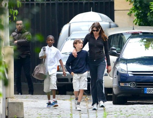 surisburnbook:  I love France. Here are former French First Lady Carla Bruni-Sarkozy and her son Aurélien out and about in the City of Lights. I love Aurélien's smart posture, casual hands-in-pockets look, and most especially those glasses. He looks like a Parisian Harry Potter — which basically just means a well-dressed squib version. How do you say a little crush in French?